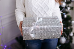 Christmas Gift. woman showing beautiful gift box. Closeup of present on christmas background Stock Photography