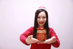 Christmas gift woman. Smiling holding present isolated on white background. girl in winter sweater showing gift wearing Santa hat. Cute, beautiful model: mixed Stock Images