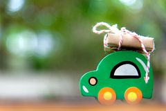 Christmas gift on wood toy car on the road, green background. stock photo