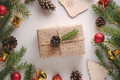 Christmas gift wrapped in craft paper decorated with spruce twig and pine cone. Christmas gift wrapped in craft paper and twine decorated with green spruce twig royalty free stock images