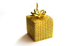 Christmas gift wrapped in gold on white bacground Stock Photos