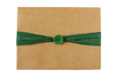 Christmas gift wrapped in kraft paper decorated with green ribbon Stock Image