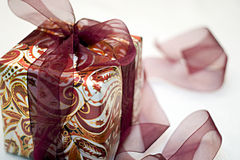 Christmas gift wrapped with red paisley paper Royalty Free Stock Image