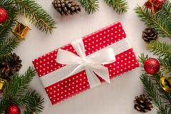 Christmas present in red paper with white polka dots and big white bow. Christmas gift wrapped in red paper with white ka dots and big white bow, surrounded by stock image