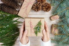 Christmas gift wrapping background. Female hands packaging christmas present wrapped in kraft paper top view. Winter holidays conc. Ept flat lay. Woman holding Royalty Free Stock Photos