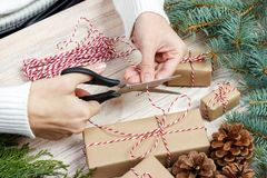Christmas gift wrapping background. Female hands packaging christmas present with red ribbon, top view. Winter holidays concept, f Stock Photos