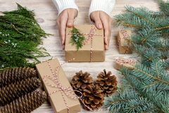 Christmas gift wrapping background. Female hands packaging christmas present with white satin ribbon, top view. Winter holidays co Royalty Free Stock Images