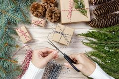 Christmas gift wrapping background. Female hands packaging christmas present wrapped in kraft paper top view. Winter holidays conc. Ept flat lay. Woman holding Stock Images