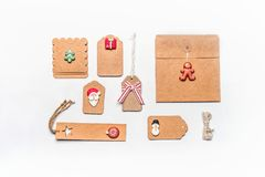 Christmas gift wrapping concept. Flat lay of various craft eco paper cardboard package and tags with decoration. Of Santa, ginger man and Christmas tree on Royalty Free Stock Image