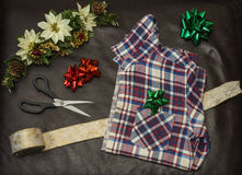 Christmas gift wrapping a men's plaid shirt. Christmas gift wrapping a men's plaid shirt with bow and ribbon Royalty Free Stock Images