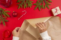 Christmas gift wrapping. Woman`s hands packing Christmas present box in craft paper stock images