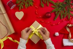 Christmas gift wrapping. Woman`s hands packing Christmas present box on red table background stock image