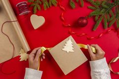 Christmas gift wrapping. Woman`s hands packing Christmas present box on red table background stock images