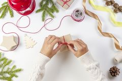 Christmas gift wrapping. Woman`s hands packing Christmas presents on white table stock images