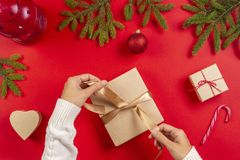Christmas gift wrapping. Woman`s hands packing Christmas present box on red table background royalty free stock photos