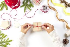 Christmas gift wrapping. Woman`s hands packing Christmas presents on white table. Christmas gift wrapping. Woman`s hands packing Christmas presents. Top view royalty free stock photo