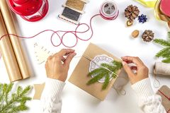 Christmas gift wrapping. Woman`s hands packing Christmas presents on white table royalty free stock image