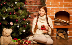 Christmas Gift , young woman near tree. Redhair woman with Christmas Gift in a house interior Stock Images