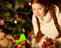 Christmas Gift , young woman near tree. Redhair woman with Christmas Gift in a house interior Stock Photos