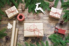 Christmas giftbox and presents wrapping in craft paper and decor on wooden board. Flat lay. Stock Photography