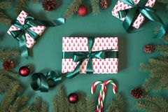 Christmas giftboxes and presents wrapping in design paper and green ribbon on green with red decor. Royalty Free Stock Image