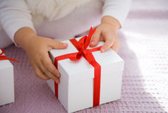 Christmas gifts. The small child opens a Christmas gift Royalty Free Stock Photo