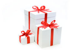 Christmas gifts. Isolated beautiful white gifts are tied up by a red tape Stock Photography