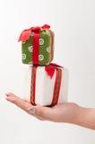Christmas gifts. Two Christmas gifts on a hand stock image