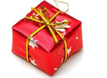 Christmas gifts. A gift wrapped in red paper and a gold bow stock image