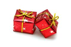 Christmas gifts. Two wrapped christmas gifts in red paper and a gold bow stock photography