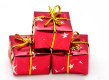 Christmas gifts. A gift wrapped in red paper and a gold bow stock photos