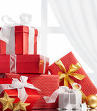 Christmas gifts. Christmas presents and ornaments against window with curtain Royalty Free Stock Photo