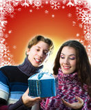 Christmas gifts. A man and a woman exchanging Christmas gifts stock photography