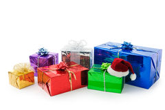 Christmas gifts. Many varicolored gifts and a santa hat on white Royalty Free Stock Photo