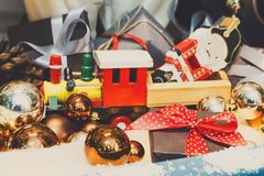 Wooden toy train as christmas gift with shiny baubles, holiday b Royalty Free Stock Photos