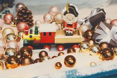 Wooden toy train as christmas gift with shiny baubles, holiday b Stock Photo
