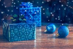 Christmas gifts and Christmas balls on a wooden table. royalty free stock image