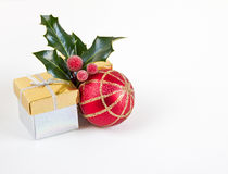 Christmas gifts, bauble and holly Royalty Free Stock Image