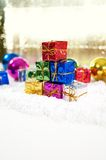 Christmas gifts with baubles and snow Royalty Free Stock Photos
