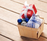Christmas gifts and baubles in a wooden basket Stock Image