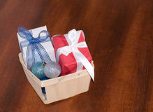Christmas gifts and baubles in a wooden basket Stock Photos
