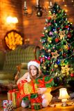 Beautiful girl in a Santa Claus hat sits on the floor near the Christmas tree and holds a lot of gifts stock photos