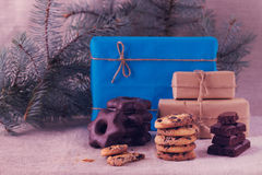 Christmas gifts and biscuits on the background of fir branches. Royalty Free Stock Photography