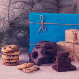 Christmas gifts and biscuits on the background of fir branches. Royalty Free Stock Photos