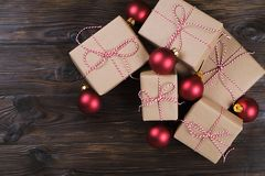 Christmas gifts box presents with red balls on wooden background Royalty Free Stock Images
