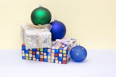 Christmas gifts in boxes and Christmas balls. On a colored background Stock Photos