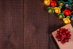 Christmas gifts boxes with garland on a wooden background. Stock Image