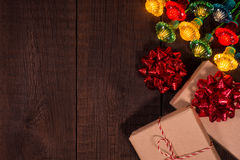 Christmas gifts boxes with garland on a wooden background. Stock Photo