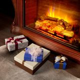 Christmas gifts boxes near fireplace Royalty Free Stock Photo