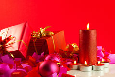 Christmas gifts and candles over red Royalty Free Stock Photos